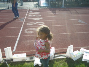 young girl helping set luminary bags back up