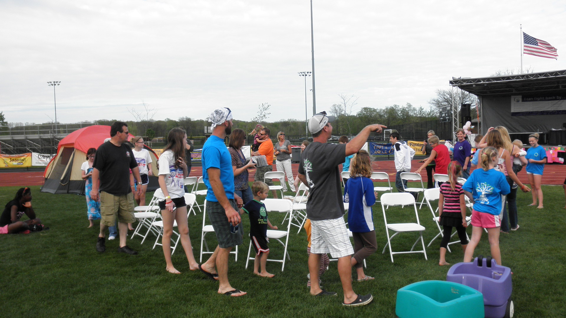 People walking around a circle of chairs for a cake walk.