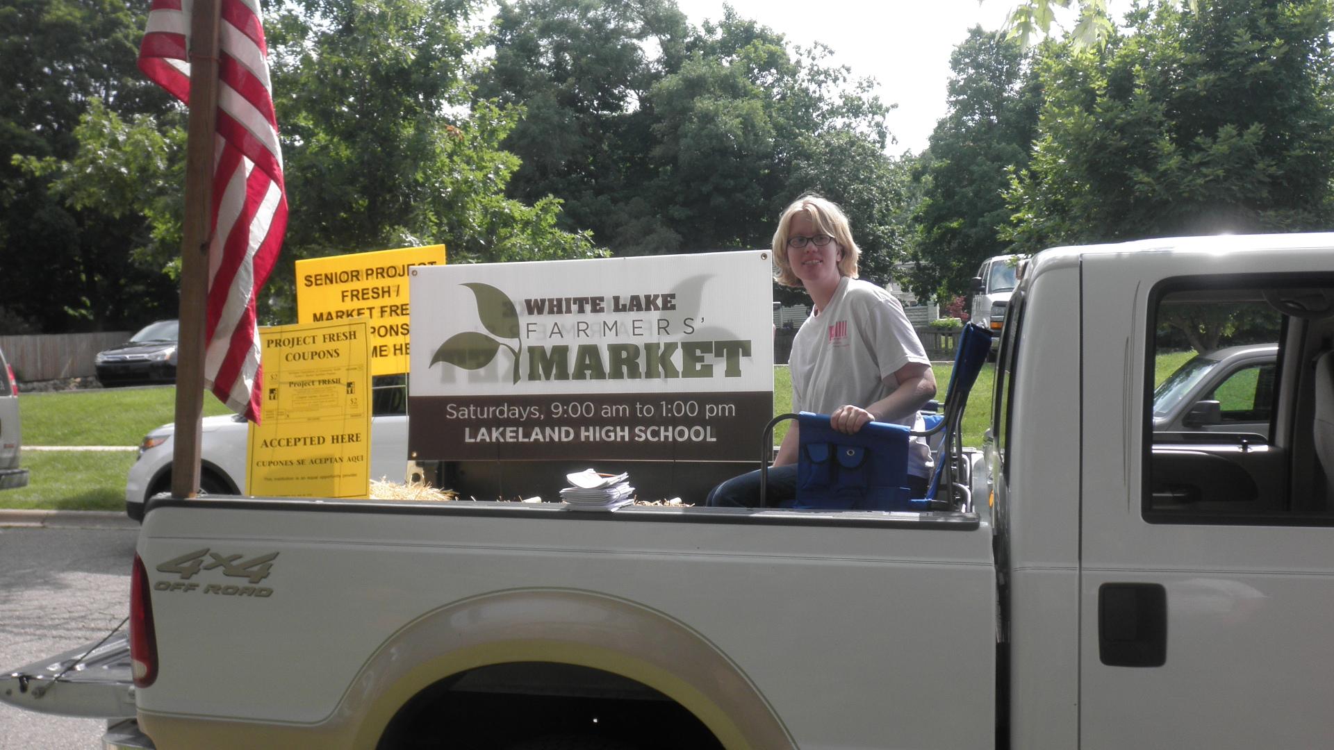 Nikki in the bed of the truck representing White Lake Farmer's Marke
